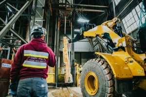 Inside a warehouse-like structure, a person wears a maroon hoodie with reflective tape on it and Thyssen Mining printed on the back. The person is also wearing a hardhat and jeans, and is facing away from the camera in the lower left quadrant of the photo. In the right half of the photo, a large yellow piece of equipment reaches toward a long metal-looking beam, which is vertical and in the center of the photo.