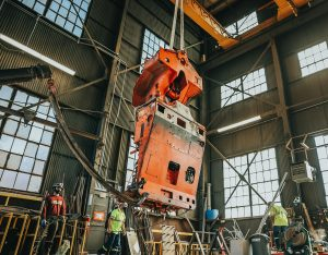 A giant orange apparatus that looks somewhat like the body of an automobile hangs from a large beam in the center of a warehouse-like room full of windows. People in hard hats and reflective vests stand on the ground around it.