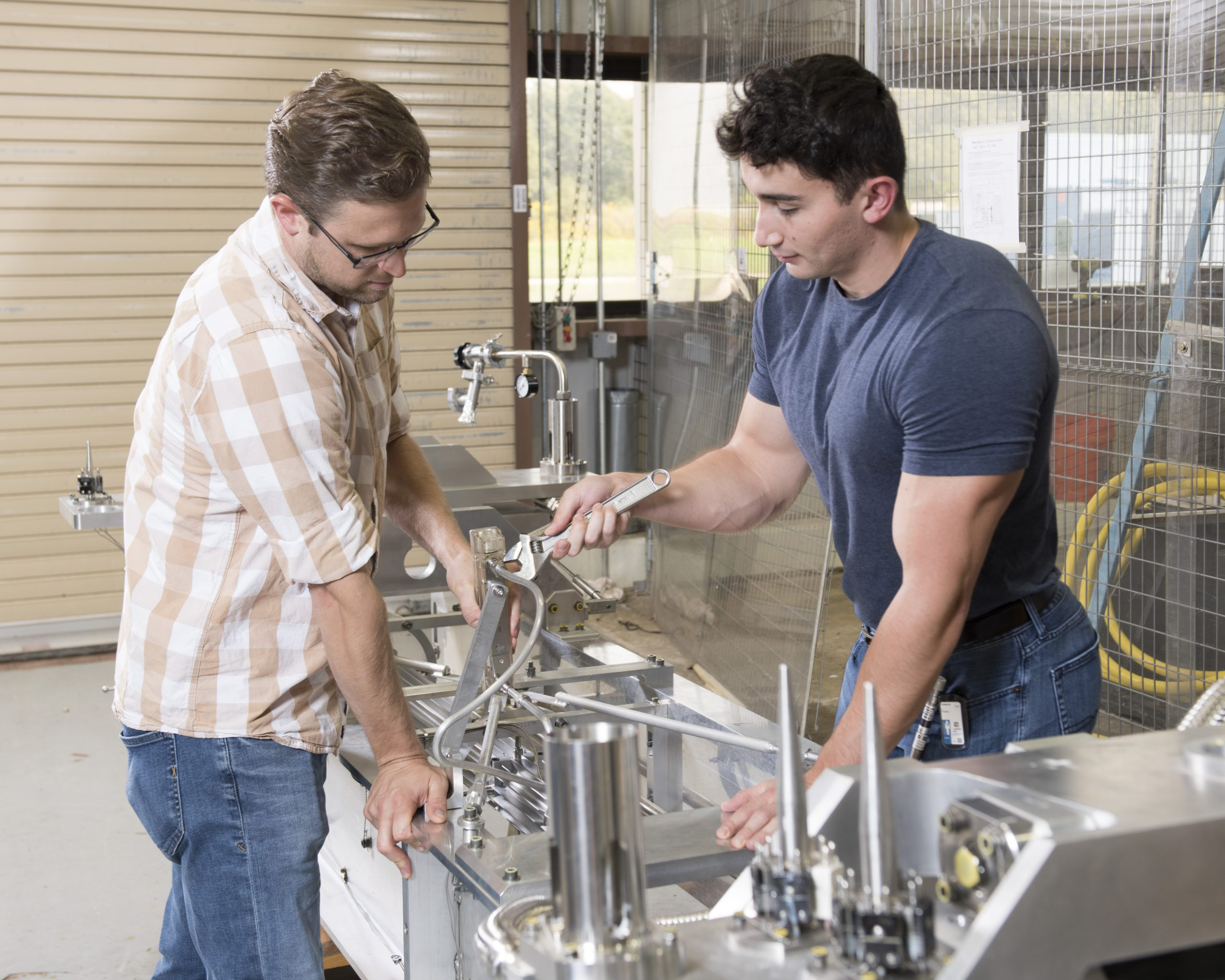 Two young men, one in glasses and a plaid shirt, one in a blue tshirt, stare at a silver-colored instrument between them. The instrument almost looks like a complicated sink with lots of nozzles and add-ons. The man in the blue shirt passes a wrench to the man in the plaid shirt.