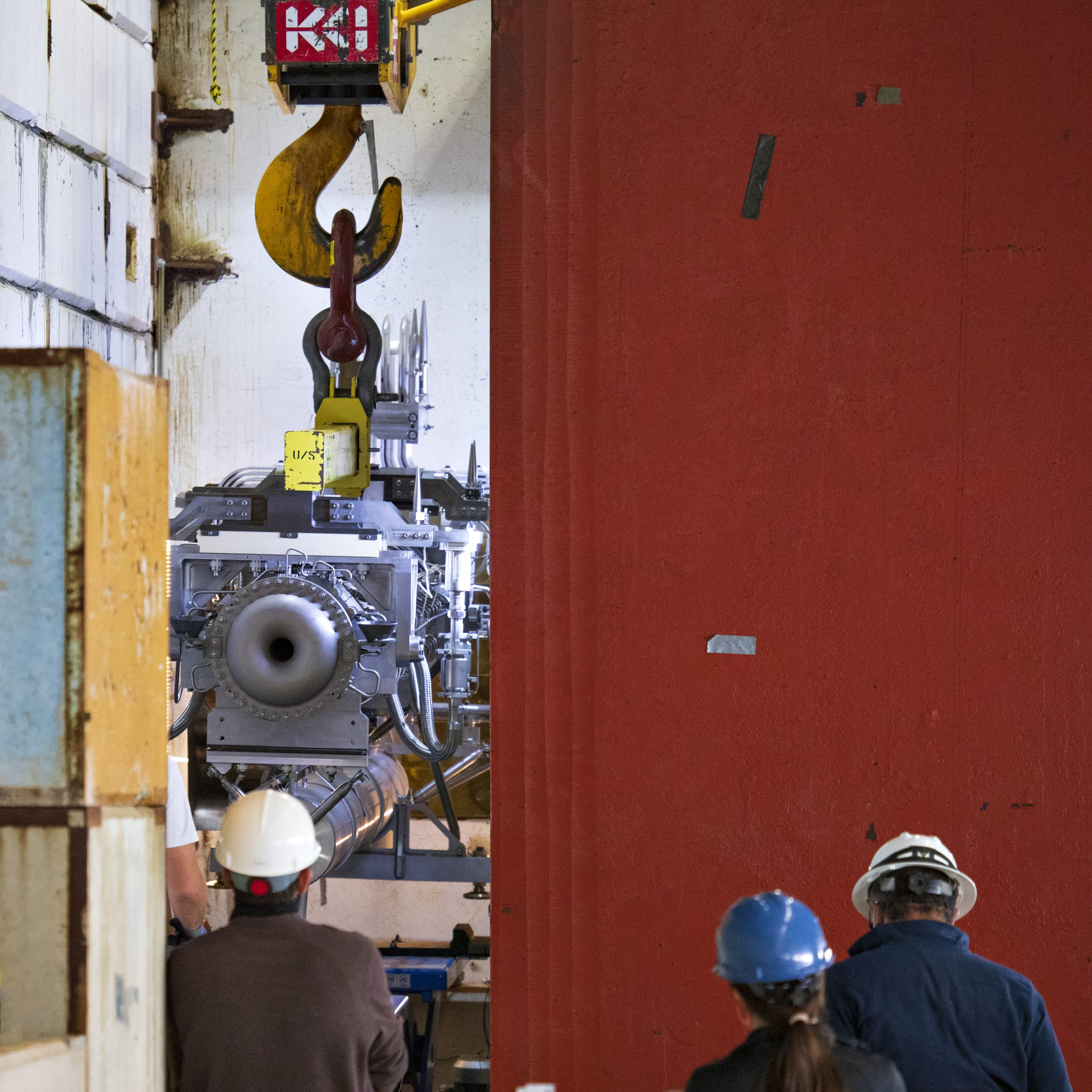 In the foreground, the backs of three people in hard hats staring at a large yellow hook holding a silver-colored piece of equipment. A large red wall is on the right half of the photo.