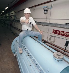Photo of a man in a white hardhat, glasses, white polo and blue jeans and tennis shoes sitting astride a large baby blue tank. He is pointing straight ahead with his right hand, left hand on his left knee.