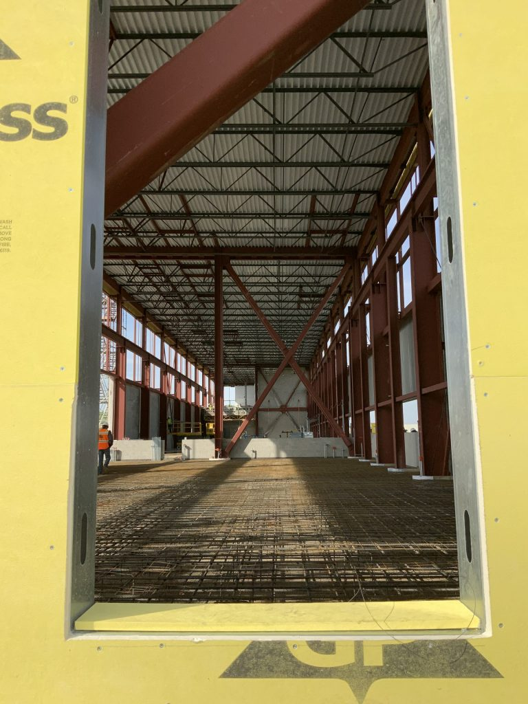 A cut-out of a window or door, framed in yellow. Inside, the frame--steel beams, the beginning of a floor, and corrugated ceiling are visible. So is a person in a hardhat and orange reflective vest walking along the left side of the photo, facing away from the camera. Blue sky peeks in the sides of the construction.