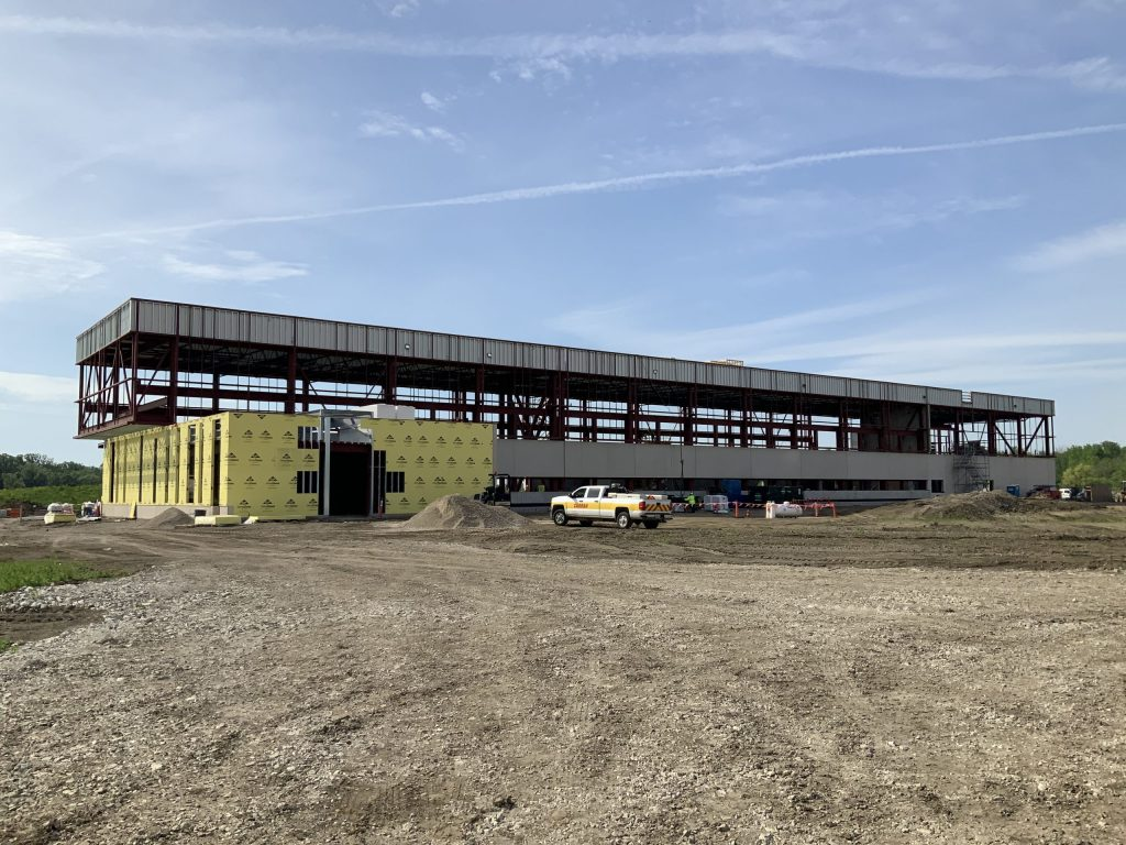 A long and thin building being constructed. The steel frame is up, the lower half of the building has yellow wraparound on the left quarter and what looks like cement on the rest of the lower half. A white pickup with a yellow stripe sits on site, and at least one person appears to be on site. Dirt fills the lower third of the photo. Blue skies above.