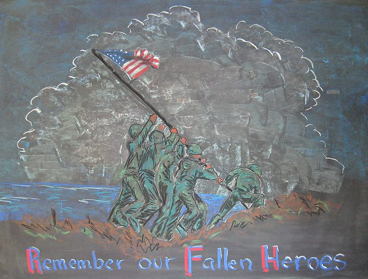 In a chalk illustration, five men in military uniforms hoist an American flag. Behind them, a body of water and a giant cloud. Under their feet, brown and green terrain. In text underneath, Remember our fallen heroes is written in red, white and blue.