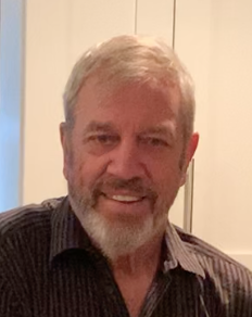 Photo portrait of a man with a gray and white beard and hair in a black collared shirt in front of an off-white background.