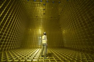 A person wearing a hardhat stands inside a bright yellow honeycomb-like box that appears to be two or three times their height.