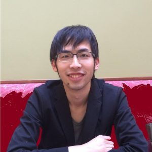 Portrait of a man with dark hair and glasses sits in a red booth-like chair and smiles, arms folded in front of him. He is wearing a black blazer and dark t-shirt.