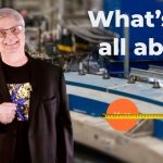 """A still of a man with gray hair and glasses in a tshirt and black blazer. Behind him, blurred instrumentation that is mainly blue and white. To the right of him, a yellow measuring tape measuring an orange circle. In the top right corner, text: """"What's g-2 all about?"""""""
