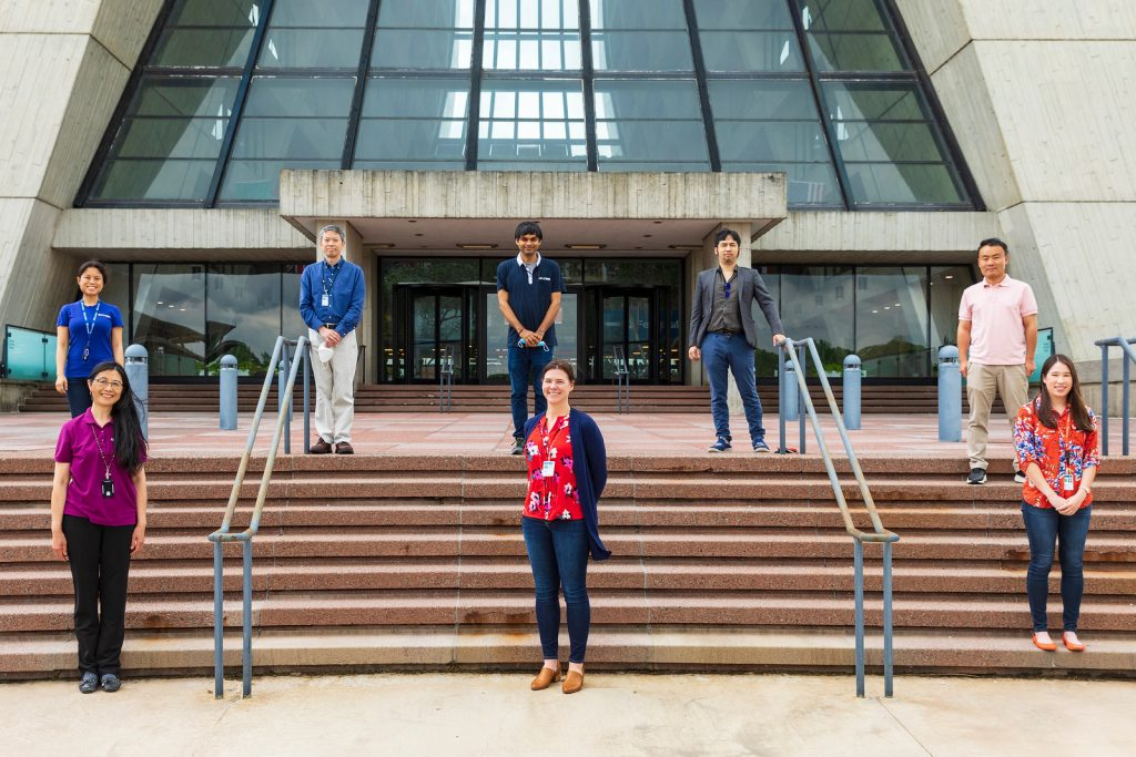 Four women and four men stand socially distanced in front of a glass and concrete building on entrance stairs.
