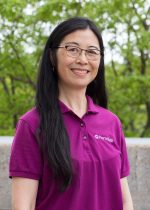 A portrait of a woman with long black hair and glasses, smiling and wearing a pink polo shirt. In the background, concrete and trees.