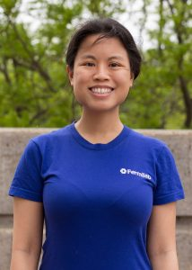 Portrait of a woman with dark hair pulled back and wearing a blue Fermilab tshirt. She is smiling. The background is trees and concrete.