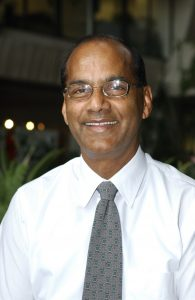 A portrait of a man smiling, wearing glasses a white collared shirt and grayish tie. In the background, blurred string lights and a green plant.