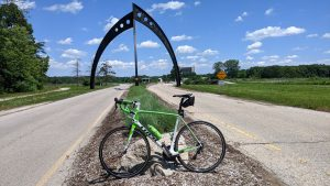 A bright green bicycle leaned against a large rock in a median. The median cuts underneath a large arch sculpture. Road and grass on either side. Blue skies with white clouds above.
