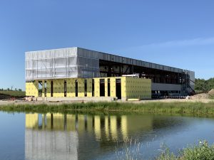 The frame of a building, with the lower half wrapped in yellow paper, sits behind a body of water surrounded by grass. Blue sky behind.