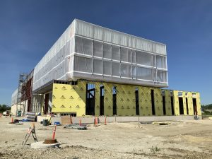 Photo of the frame of a building covered in a see-through white material on the upper floor and yellow paper on the lower floor. Scaffolding on the left side of the building. It sits on a sandy construction site with blue sky behind.