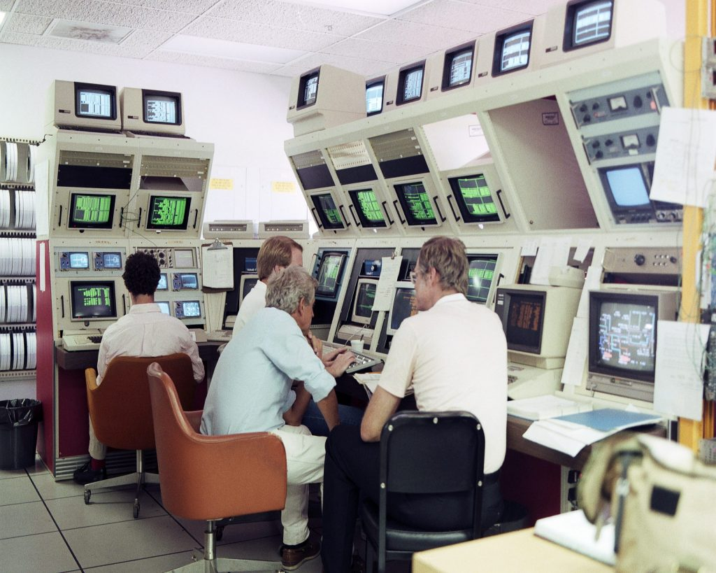 Four men sit at an L-shaped, ceiling-high set of computers.