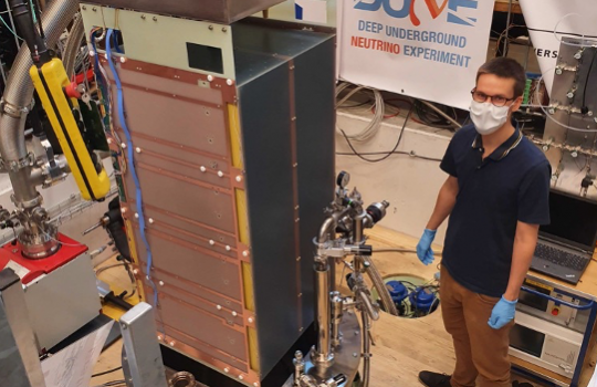 """A large box-like structure sits on a round platform. Behind it, a banner that says """"DUNE."""" To the right, a man with short hair wears glasses, a face mask, blue surgical gloves, a blue shirt and brown pants."""