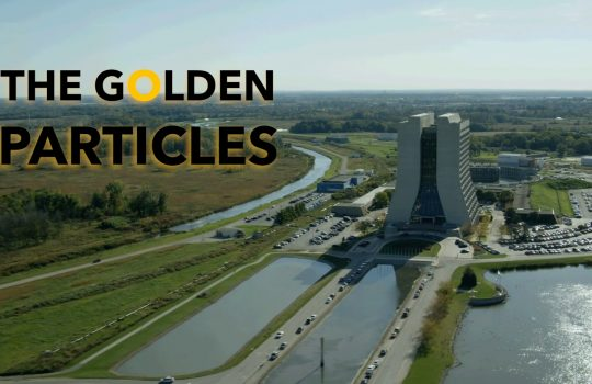 """""""The Golden Particles"""" in text, with a glowing yellow """"O"""" in the word Golden. Text is oerlaid onto photo of Fermilab campus, showing a 16-story concrete building and reflection pool to the right, prairie to the left and blue skies."""