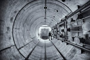 A black and white photo taken inside what appears to be a large and long tunnel. Along the right wall of the tunnel, five parallel rows of pipe punctuated by spool-like gadgets gadgets runs its length. A person at the far end props a leg up on the side of the tunnel underneath the pipes as if to inspect. Out the end of the tunnel, a large cabinet-like structure, to the left of that, a ladder.