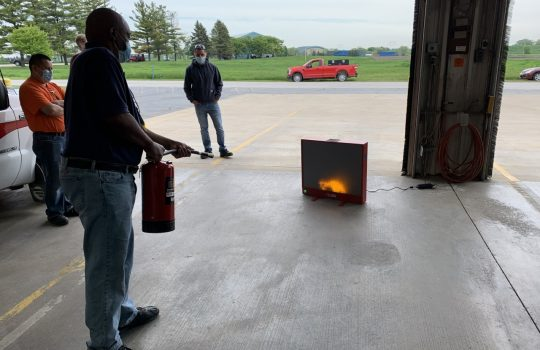 In the high bay facing out, a man uses a fire extinguisher to point at a small simulated fire. Several men look on.