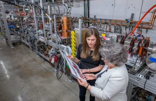 Two women stand side by side looking at an image of a red vessel in front of a long science experiment that takes up the rest of the photo. The woman with gray hair, on the right, and the woman with long brown hair on the left both hold the document with both hands.
