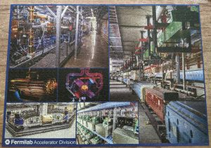 """Photo of a completed puzzle that reads """"Fermilab Accelerator Division"""" and is a photo collage of different scientific experiments in close-up and mid-range shots."""