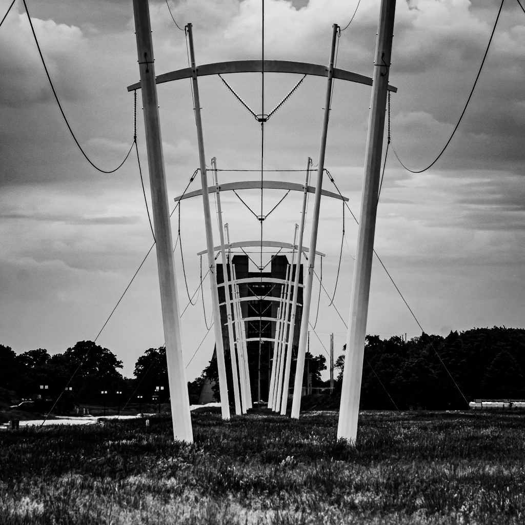 In this black-and-white photo, what appear to be electrical poles form a concentric outline of a tall concrete building behind them.