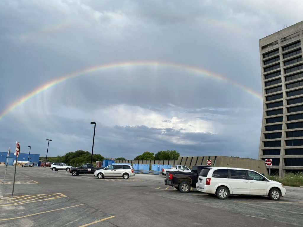 Rainbow spans from outside left edge of photo to behind a concrete high-rise on the right, over a parking lot with several vans and trucks.