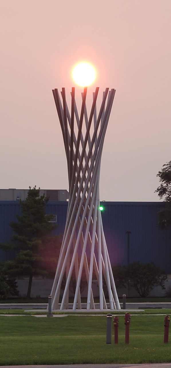 A photo of an orange sun right above a large vertical sculpture in front of a blue building.