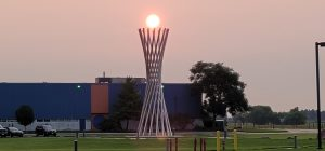 A photo of an orange sun right above a large vertical sculpture in front of a blue building, pinkish hazy sky behind.