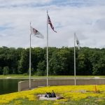 Three flags fly on tall flagpoles in front of a concrete retaining wall beside a body of water. Behind that, forest and a blue sky full of white clouds.