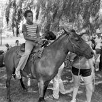 A school-aged boy in a striped shirt and jeans rides a horse led by an older girl in a T-shirt and shorts in this black-and-white photo. People and foliage in the background.