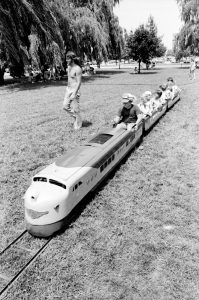Kids ride a small tram made to look like a modern train down a track in this black-and-white photo. A young man or teenage boy in long jeans and no shirt walks beside. Grass underneath, trees and sky in background.