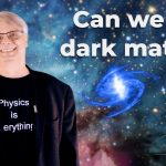 """A man with short gray hair and glasses smiles. He is wearing a black blazer and a black T-shirt that reads """"Physics is everything."""" He is in front of a starry sky. To his right, text that says """"Can we find dark matter?"""" In the lower right-hand corner, an illustration of an atom."""