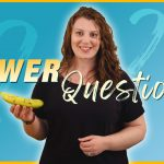 """A woman with long wavy brown hair wearing a black T-shirt holds a banana in one hand. She is in front of a turquoise gradient background with question marks on it. In the lower left corner is an illustration of a banana. Across the middle the text """"Viewer Questions!"""""""