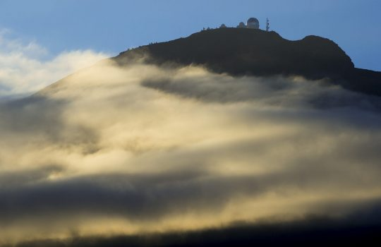 Photo of a dome-shaped building, likely an observatory, atop a mountain, which gold mist surrounds. Blue sky and silhouette of birds above.