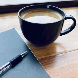Photo of a coffee in a dark mug, ballpoint pen and blue folder or notebook on a wooden table.