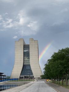 On the left, a 16-story concrete building. A rainbow arcs out of its right side over a tree in the right side of the photo. Cloudy sky behind.