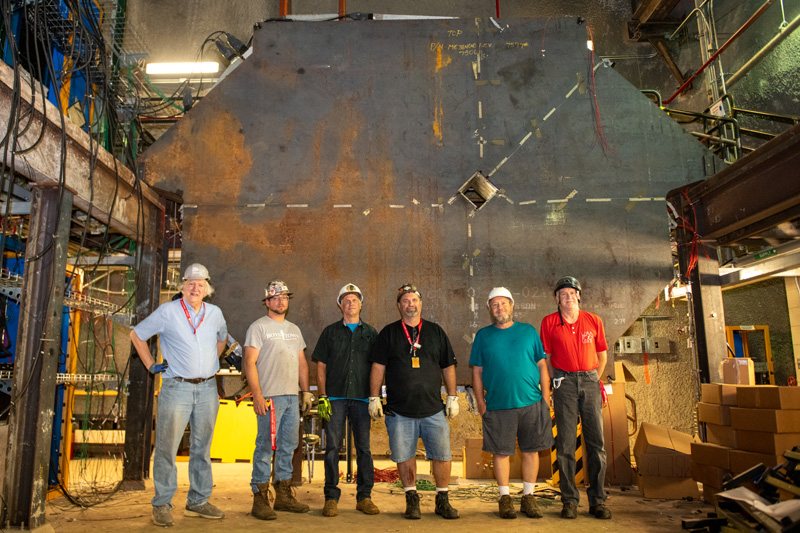 The decommissioning team stands in front of a large component.