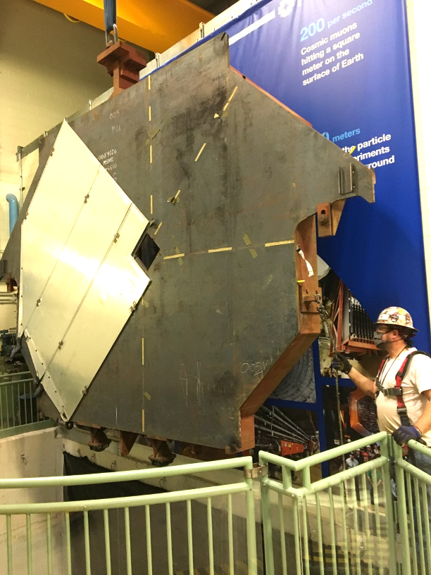 A detector plane in the foreground with a worker guiding it.