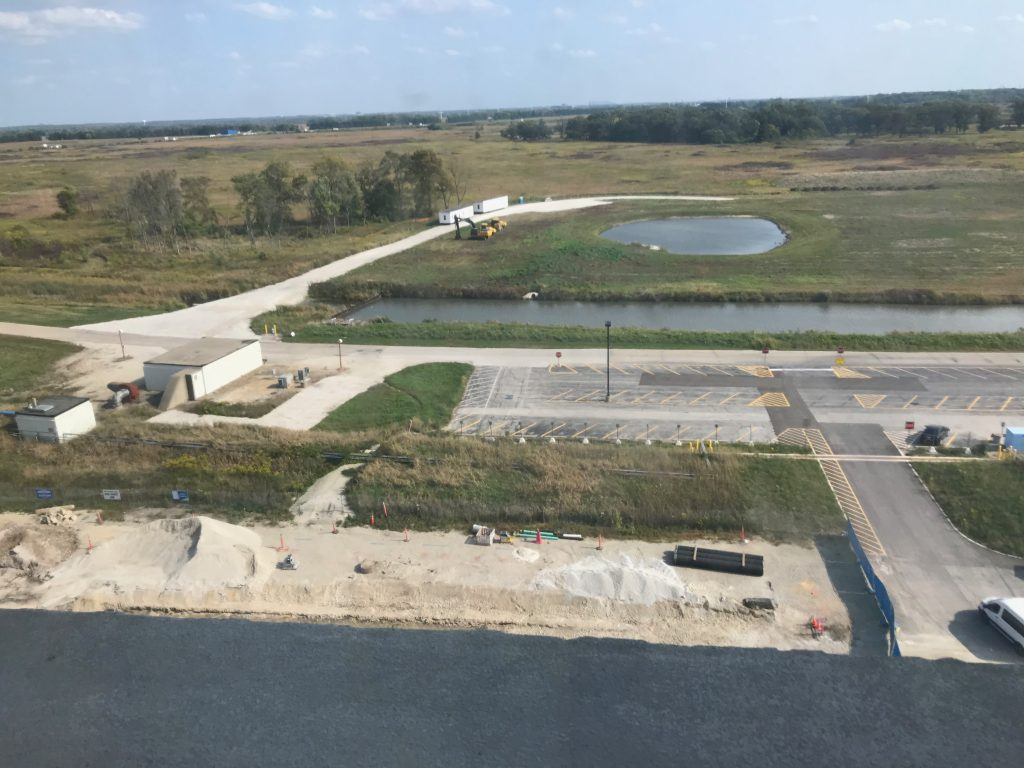 A parking lot, long body of water, some sand from construction, some construction equipment, mostly grass.