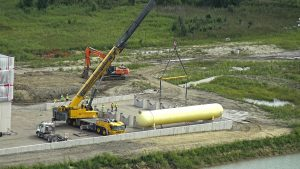 The large yellow tank sits on two holders, the two straps the crane used to lift it released on the construction site.