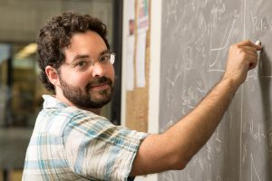 Scientist and 2021 URA Early Career Award winner stands at a chalkboard working on equations.