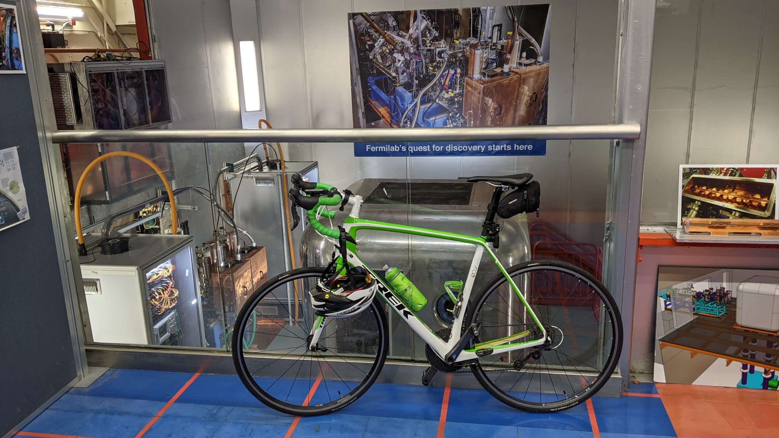 A white and green Trek bike on a blue and red striped floor with a glass wall and equipment behind.