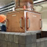 A person in PPE peers out from behind a large copper cube with doors with slate-colored blocks around its base.