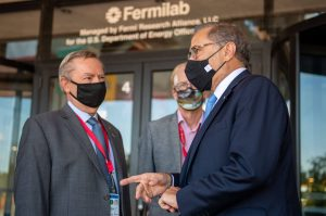 Three men in suits and facial coverings stand at the entrance of a Fermilab building.