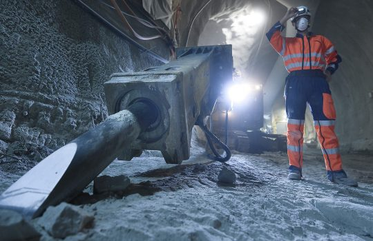 A person in a face mask and construction clothing adjusts the light on their hardhat stands in a gray tunnel near equipment. Behind, a large light shines.