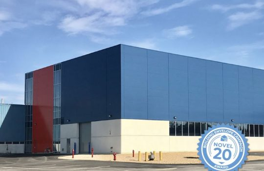 """Photo of one end of a large rectangular building that's concrete, blue, gray and red with blue sky above. An award logo is superimposed in the lower right corner. It reads: """"Building Envelope Campaign Novel 20 Award."""""""