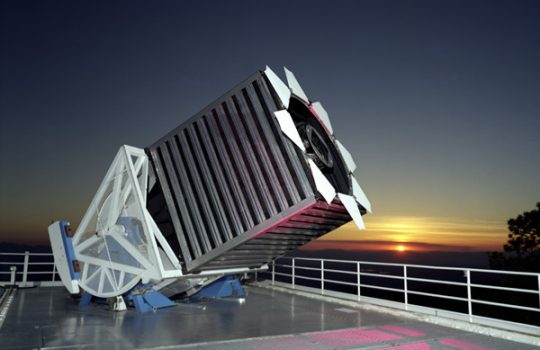 A large telescope on a rooftop, the sunset behind it