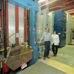 Two scientists stand in front of large equipment